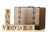 stock photo of bon voyage  - A leather suitcase sitting behind rustic alphabet blocks that are arranged to say  - JPG
