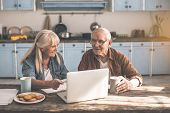 Portrait Of Cheerful Mature Husband And Wife Using Laptop In Kitchen. Woman Is Pointing At Screen Wi poster