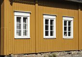 stock photo of graff  - Three white windows in the yellow wall of wooden house - JPG