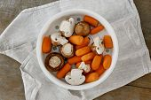 Healthy Vegetarian Food. Raw Carrots And Mushrooms In Saucepan For Steamed On Wooden Table, Top View poster