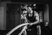 Muscular Powerful Aggressive Man Training With Rope In Functional Training Fitness Gym poster