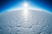 Salar de Uyuni salt flat with salt patterns and sun close to the horizon, Bolivia poster