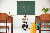 Upset teenage girl sitting under chalkboard with word Loser in classroom. Bullying in school poster