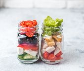 Greek Salad And Caesar Salad In Glass Mason Jar On Gray Background.homemade Healthy Caesar Salad And poster