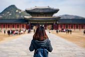 Young Asian Woman Traveler With Backpack Traveling Into The Gyeongbokgung Palace  With Blue Sky And poster