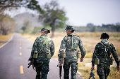 Asian Army Soldier Return To Base After Completing Military Mission. Armed Infantry Walking In The F poster