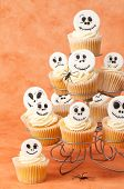 Halloween cupcakes decorated with skeleton faces on orange background