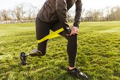 Cropped photo of disabled girl in tracksuit exercising and doing lunges with prosthetic leg on grass poster