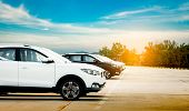 Luxury White And Black New Suv Car Parked On Concrete Parking Area At Factory With Blue Sky And Clou poster