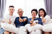 Asian Family With Adult Children And Senior Parents Giving Thumbs Up And Relaxing On A Sofa At Home poster