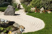 stock photo of sand lilies  - little zen garden with sand rocks and flowers - JPG