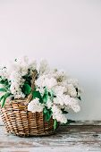 Bouquet Of Fresh White Lilac Flowers In Wicker Basket On Wooden Table, Rustic Floral Home Decoration poster
