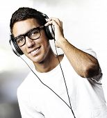 portrait of youn man with glasses listen to music in a living room