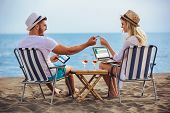 Happy Smiling Couple Surfing The Net And Enjoy The Summer At Tropical Beach Using Laptop, Digital Ta poster