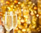 Two glasses of champagne with lights in the background. very shallow depth of field, focus on near g