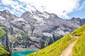 Beautiful Oeschinensee Lake Near Kandersteg In Switzerland. Turquoise Lake Surrounded By Steep Mount poster