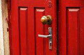 Red Wooden Door With Round Ornate Handle And Traditional Handle Slightly Open poster
