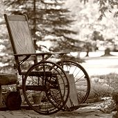 picture of antique wheelchair  - Old wooden wheelchair sits waiting in the garden - JPG
