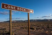 A Sign To Lone Rock In An Empty Desert Landscape. poster