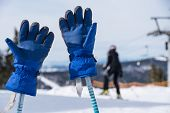 Ski Gloves Stuck On Ski Poles In Snowy Ski Resort - Close-up poster