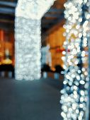 Blurred Cold White Lights Looked Festive And Beautiful Bokeh Background. Entrance In City Mall With  poster