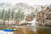 inflatable whitewater kayak and packraft on a shore of mountain river in heavy springtime snowstorm  poster