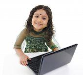 Niña India usando una laptop en mesa, aislado sobre fondo blanco