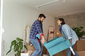 Couple In Love Moving In Together, Having Fun While Carrying An Armchair And Setting Up The New Furn poster
