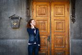 Young Smiling Woman Denim Clothing Standing Over Old Fashioned Historical Wooden Door, Rusty Postbox poster