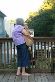 Senior Woman Holding Puppy Vertical
