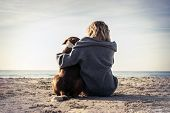 Young Woman Sitting And Hugging Dog On The Beach. Friendship Concept - Woman And Dog Sitting Togethe poster