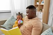 family, fatherhood and people concept - happy african american father reading book for baby daughter poster