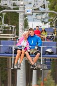 Cuddling young couple sitting on chair lift in the pinewood