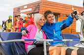 Cheerful couple sitting on chair lift man pointing