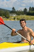 Young muscular sportsman kayaking in the sunshine