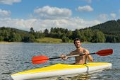 Young sportsman kayaking on sunny day on lake