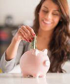 Happy Woman Putting Note In Piggy Bank, Indoors