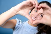 portrait of attractive happy smiling teen making heart of her hands, love holiday valentine symbol o