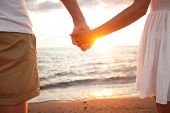 Summer couple holding hands at sunset on beach. Romantic young couple enjoying sun, sunshine, romanc