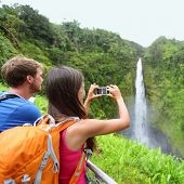 Tourist couple on Hawaii taking pictures of the famous Akaka Falls waterfall on Hawaii, Big Island, USA. Happy cheerful young multicultural couple tourists on travel.