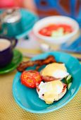 Delicious breakfast with eggs Benedict, bacon, coffee and vegetables