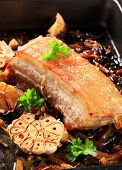 stock photo of pork belly  - roasted pork belly with grease in a black tray - JPG