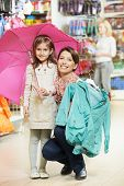 image of outerwear  - woman and little girl choosing and trying on raincoat during shopping at outerwear supermarket - JPG