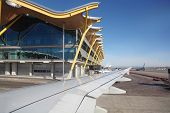 MADRID - MARCH 7: Wing of aircraft and Madrid Barajas Airport building on March 7, 2012 in Madrid, S