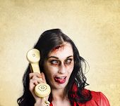 stock photo of gruesome  - Unreliable female zombie administration clerk handing over a telephone receiver late with a dead phone line - JPG