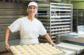 stock photo of bread rolls  - Female baker baking fresh bread rolls in the bakehouse - JPG