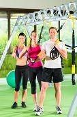 Gruppe von Menschen trainieren mit Schlingentrainer oder suspensión entrenador en Fitnessstudio