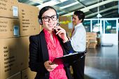 Young woman in a suit with headset in a warehouse, she is from the Customer Service, a coworker stan