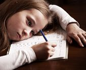 Child doing homework. Sad girl writing, reeding