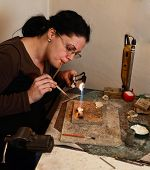 pic of blow torch  - Female jeweller blowing a torch to melt metal for making a brooch in her workshop - JPG